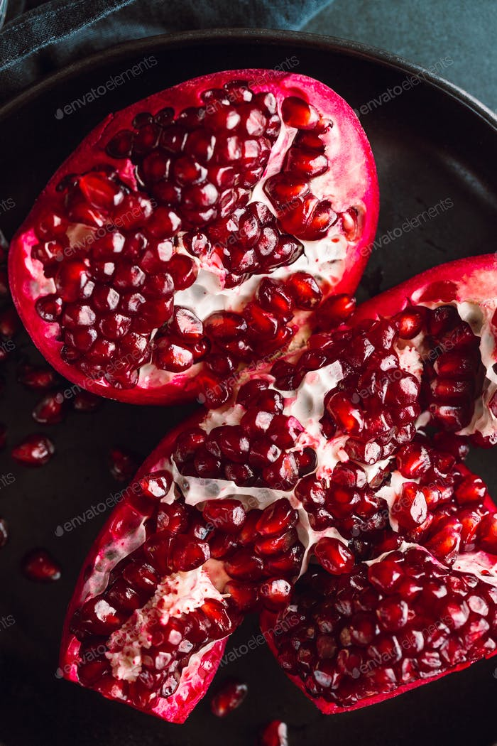 Top down view on a ripe pomegranate in a black plate