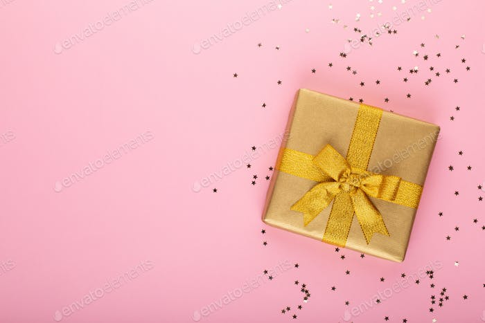 Gift or present box and stars confetti on color table top view.