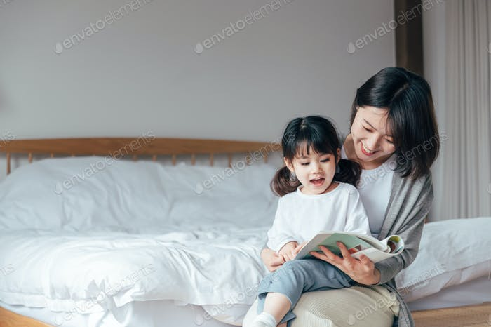 Mother and daughter reading books in bedroom