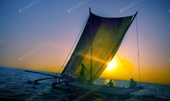 Fishermen on a catamaran at Sunset Concept