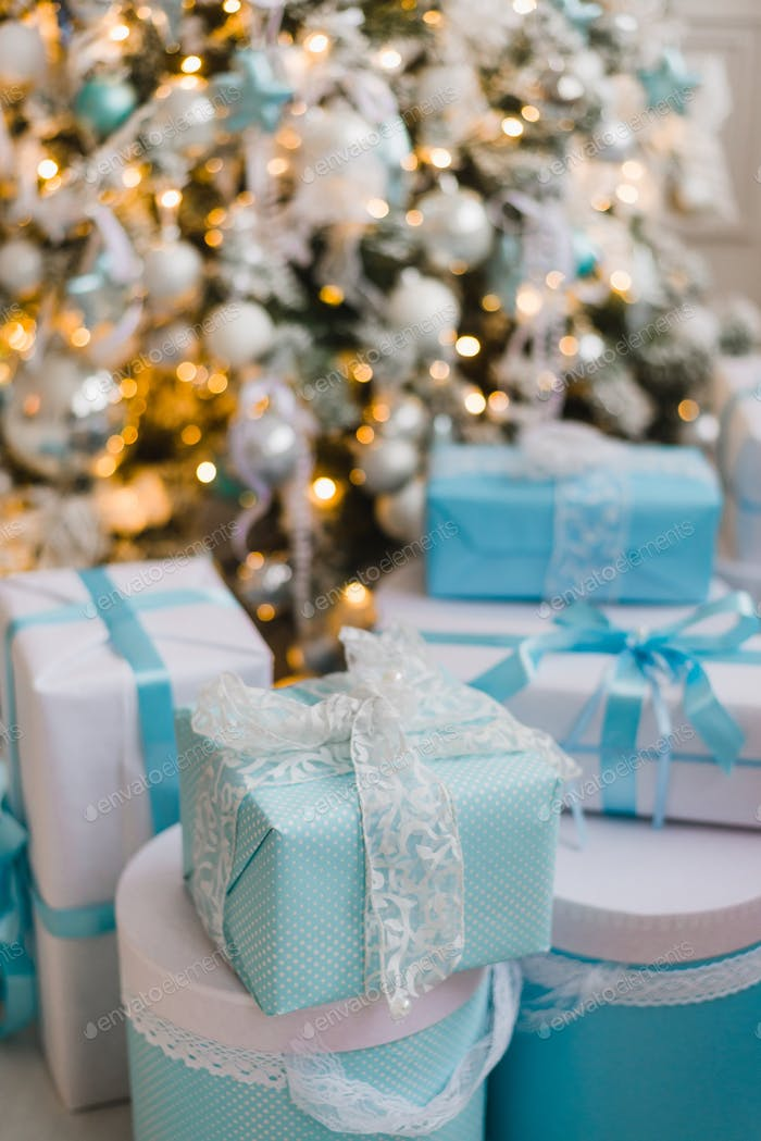 Christmas gift boxes with blue bow and bokeh lights on wooden surface