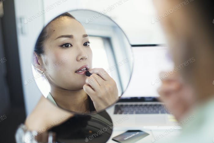 A business woman preparing for work, putting on lipstick and holding a mirror.