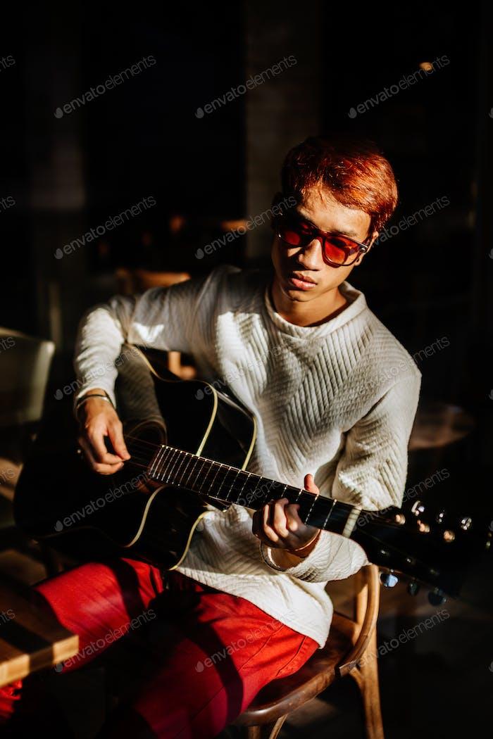 asiatischer gitarrist artiist mann spielen gitarre im café