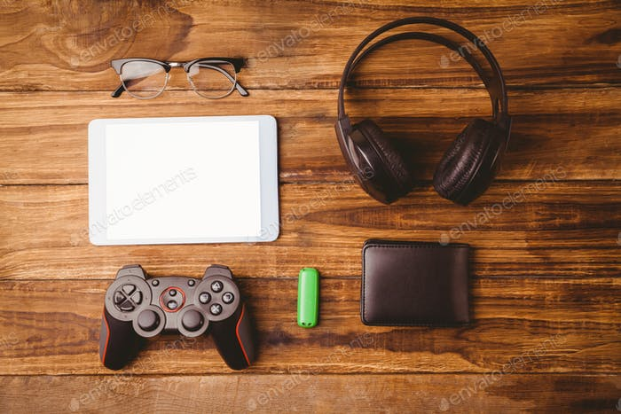 Tablet and music headphone next the joystick USB key and glasses on wooden table