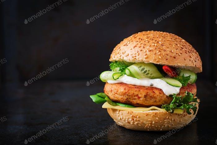 Big sandwich - hamburger with juicy chicken and tartar sauce on black background