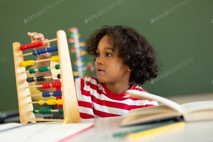 Boy learning mathematics with abacus at desk in classroom at elementary school