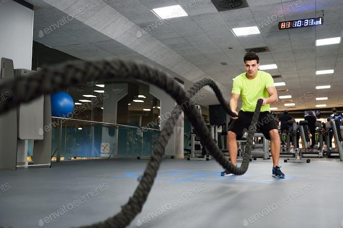 Homme avec des cordes de combat exercice dans la salle de fitness.