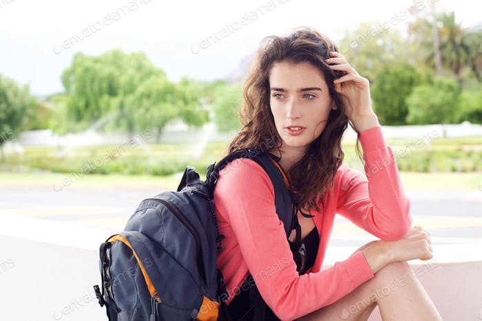 Young traveler woman sitting outside waiting with bag
