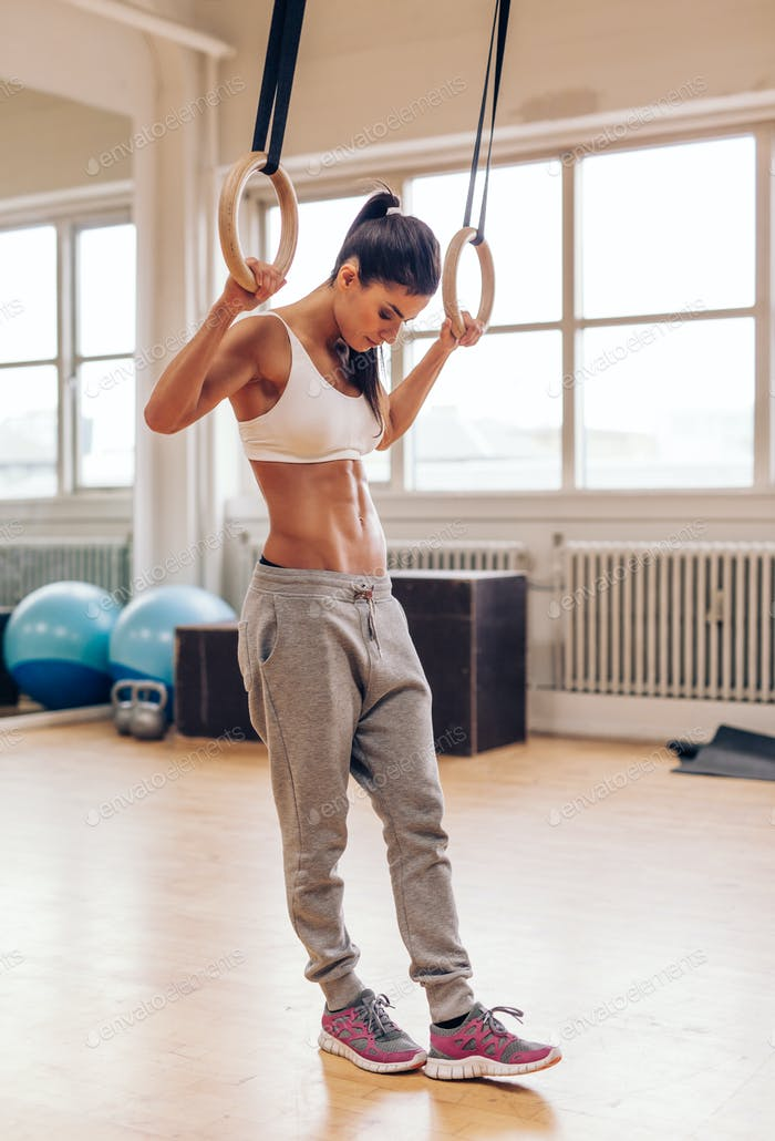 Determined woman exercising with gymnastic rings in gym