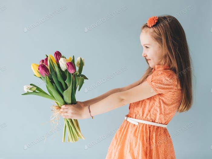 Kleines Kind mit einem Bündel von frischen Blumen