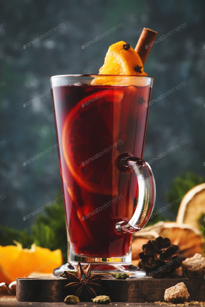 Christmas mulled red wine with spices and fruits in tall glass on wooden rustic table