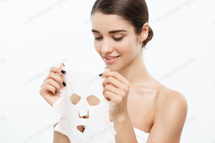 Beauty Skin Care Concept - Beautiful Caucasian Woman applying paper sheet mask on her face white