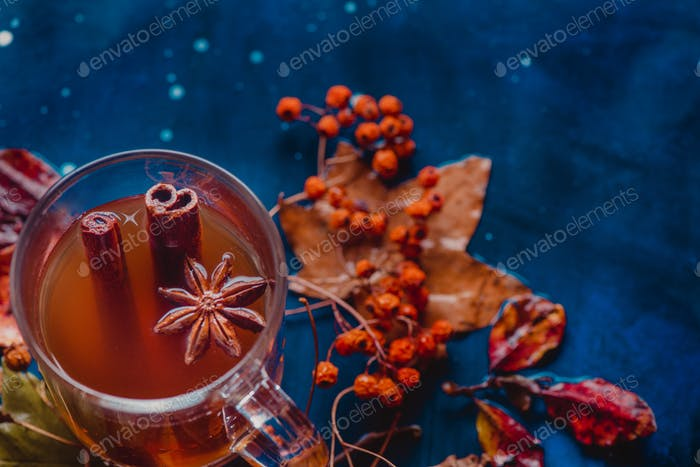 Tea with cinnamon in an autumn still life with fallen leaves and ash berry on a wet wooden