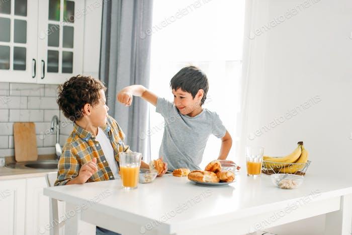 Two siblings tween boys real brothers having breakfast on kitchen