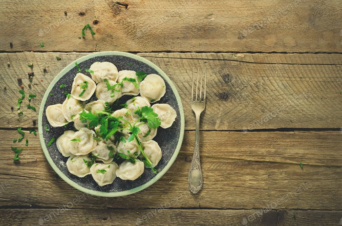 Traditional russian pelmeni, ravioli, dumplings with meat on wooden table with flour, parsley, quail