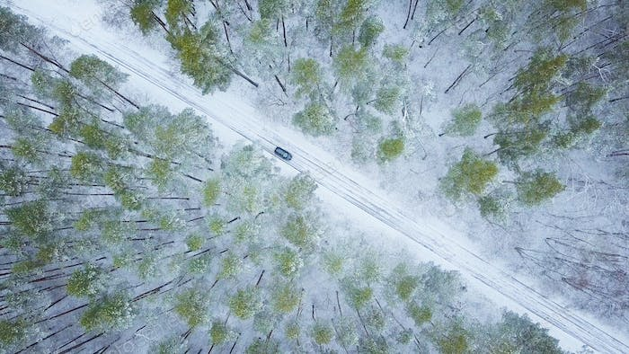 Aerial view on car driving through winter forest road. Scenic wi