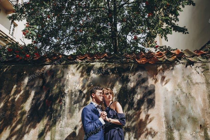 Stylish couple embracing in rainy european city street