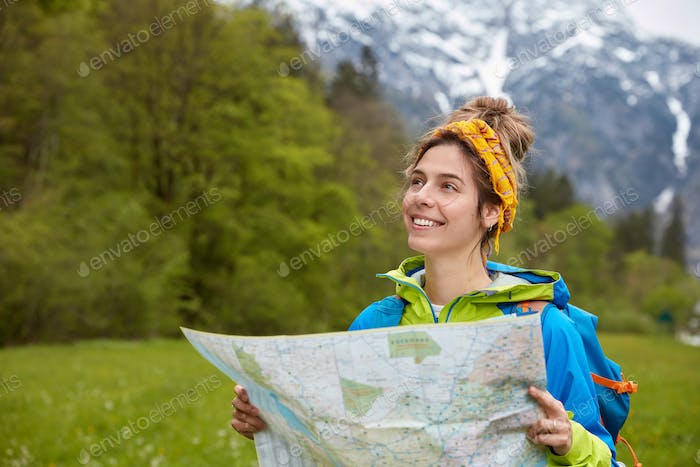 Joyful woman traveler searches right direction on tourist location map, wanders in green meadows wit