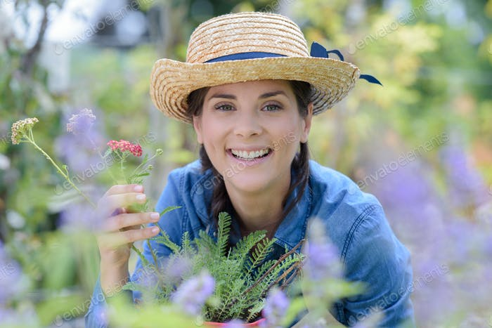 happy smiling young woman with flowers at garden