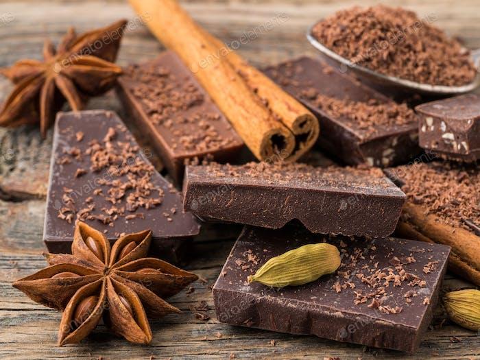 zerbrochene Stücke von Schokolade, Anisstern, Zimtstangen, Krume auf alten hölzernen Hintergrund