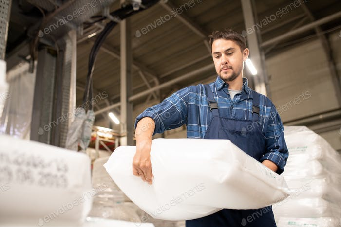 Young man in workwear carrying heavy white sack with polymer granules