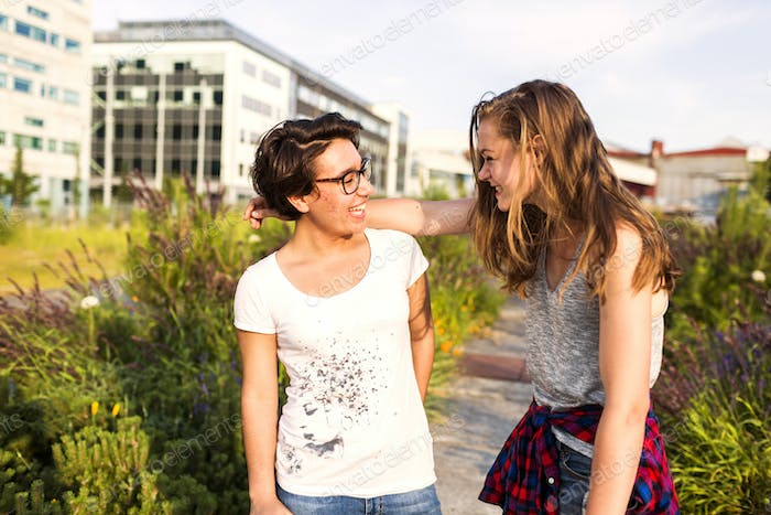 Smiling female friends with arm around talking at park