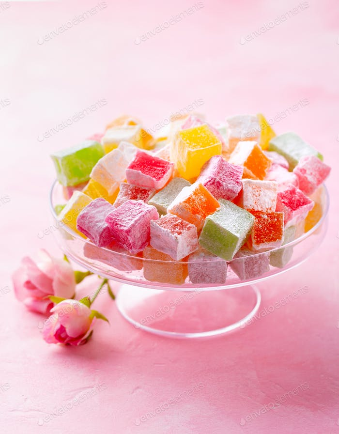 Verschiedene türkische Köstlichkeiten auf Glas-Kuchenständer. Rosafarbener Hintergrund. Kopierraum.