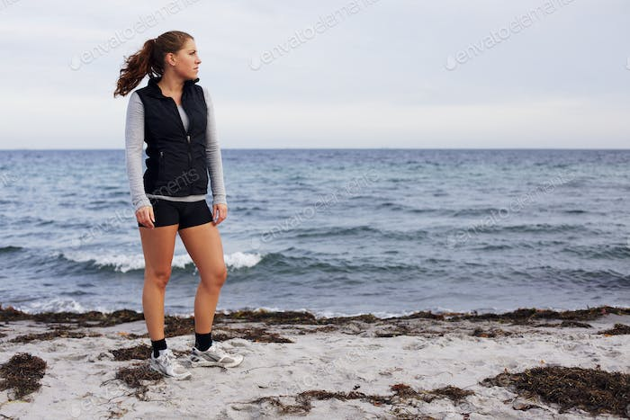 Beautiful young woman standing on beach looking away