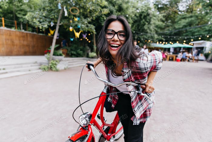 Beautiful girl in checkered shirt posing on bicycle and smiling. Outdoor shot of amazing female mod
