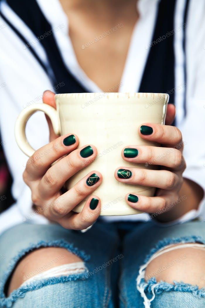 Стильная модная девушка с чашкой кофе и зеленым маникюром в джинсах. Мода, уход, красота