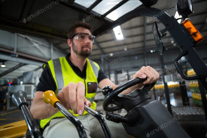Factory worker driving forklift
