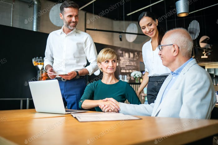 Group of business people signing a contract with handshake