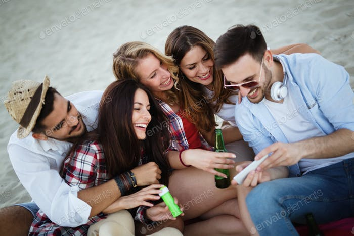 Happy young group of people taking selfies on beach