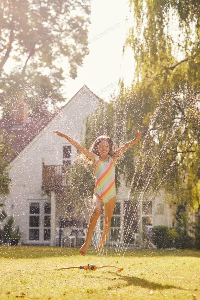 Girl Wearing Swimming Costume Having Fun In Summer Garden Playing In Water From Garden Sprinkler