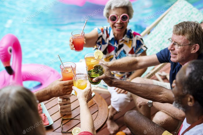 Group of diverse senior adult enjoying beverage by the pool toge
