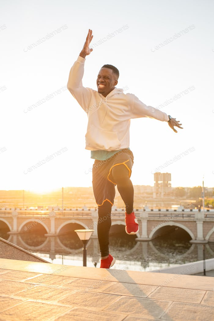 Ecstatic sportsman of African ethnicity jumping over upper step of staircase