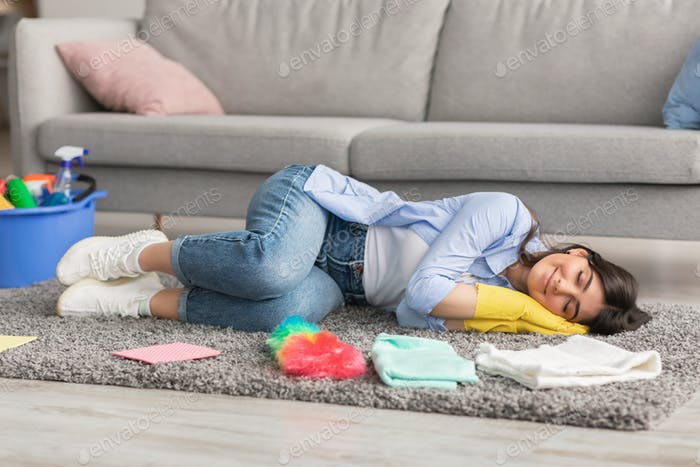 Tired woman lying on floor carpet and sleeping