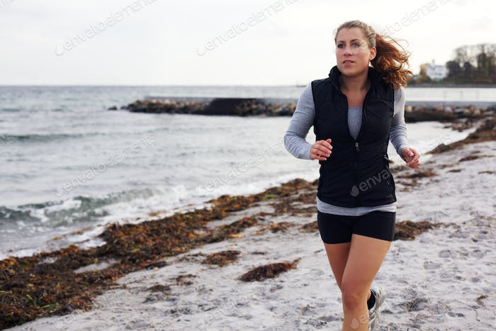 Young attractive woman jogging on a sandy beach