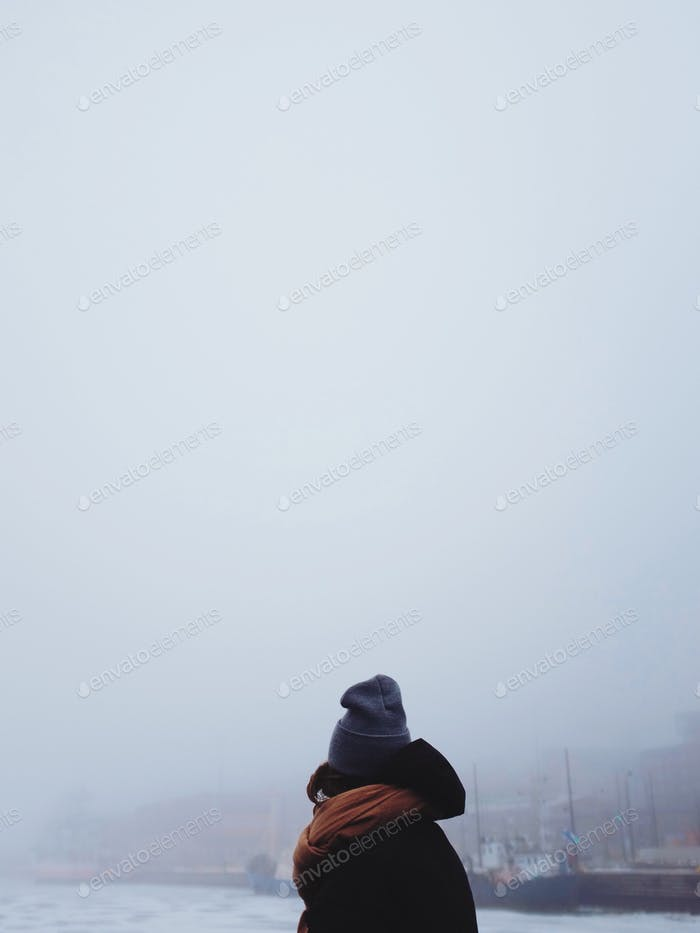 Woman framed agains a foggy sea view
