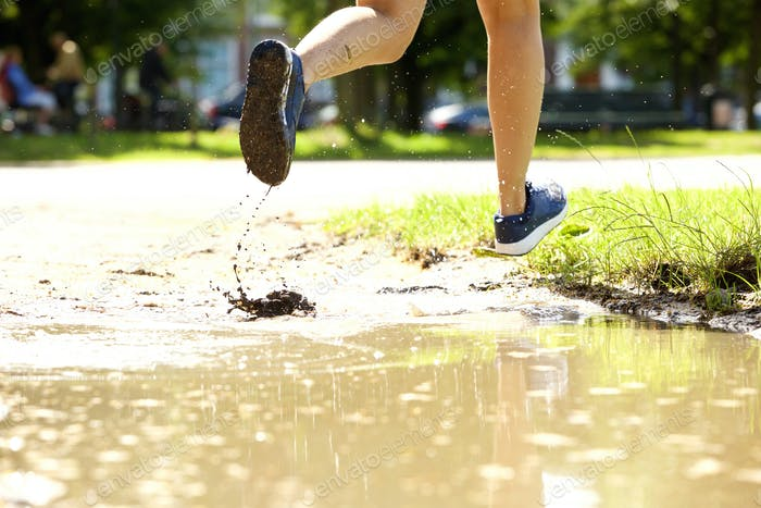 Female runner in mud puddle