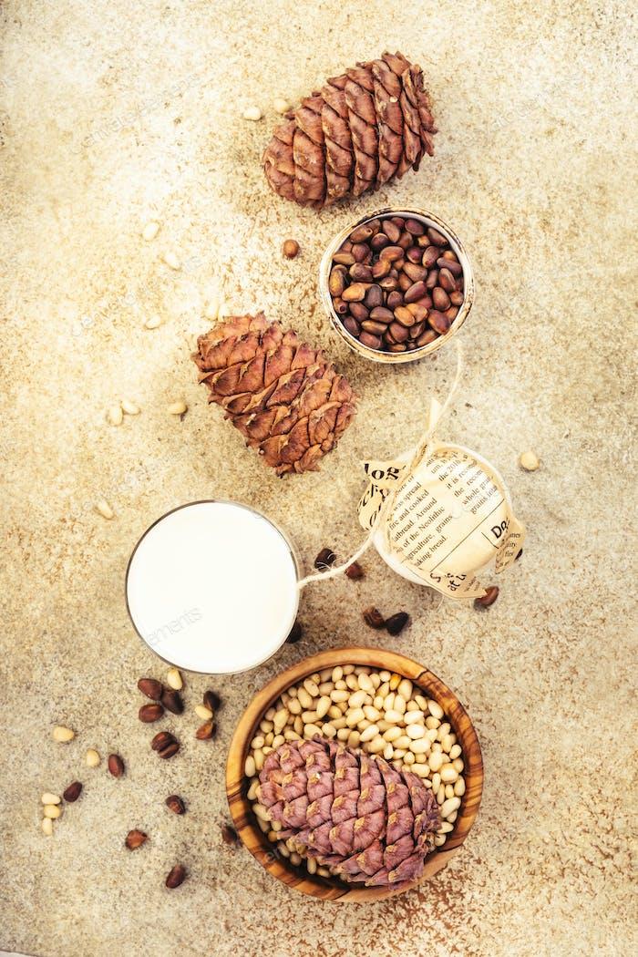 Zedernussmilch, beigefarbener Tischhintergrund. Alternative Milch ohne Milchprodukte. Gesunde vegetarische Lebensmittel