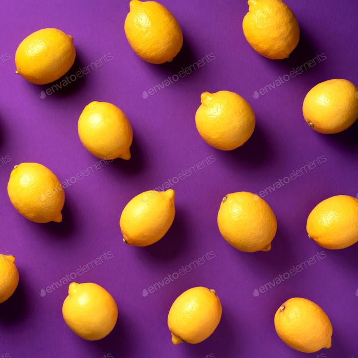 Food pattern with lemons on violet paper background. Top view. Summer concept. Vegan and vegetarian