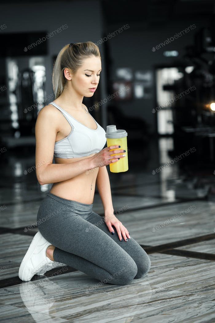 Beautiful athletic girl  poses in the gym with a yellow shake