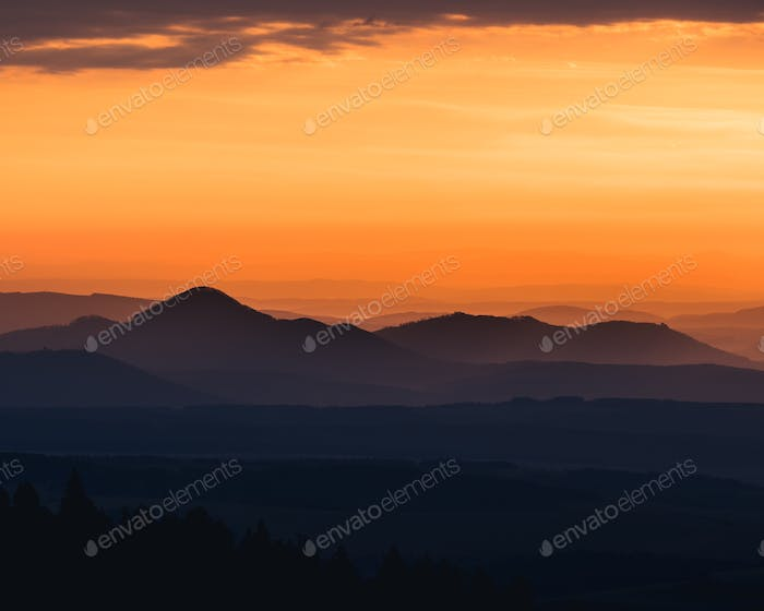 Tranquil landscape of mountains silhouettes during sunrise