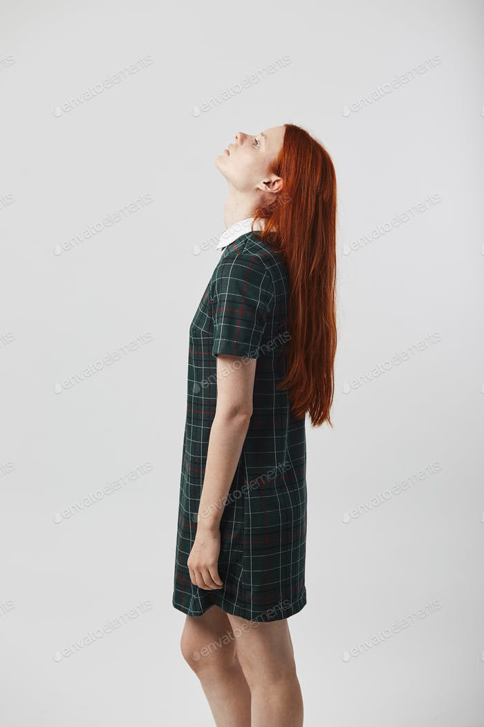 Beautiful redhead long-haired girl in a green checkered dress stand on the white background in the