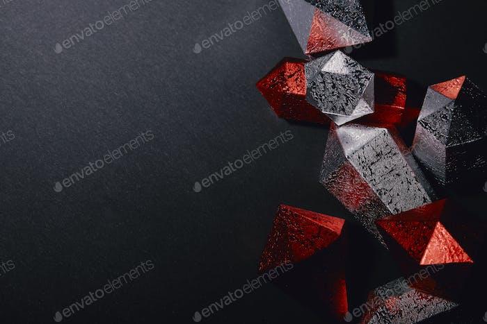 Draufsicht auf glänzende facettierte rote und silberne Edelsteine auf schwarzem Hintergrund