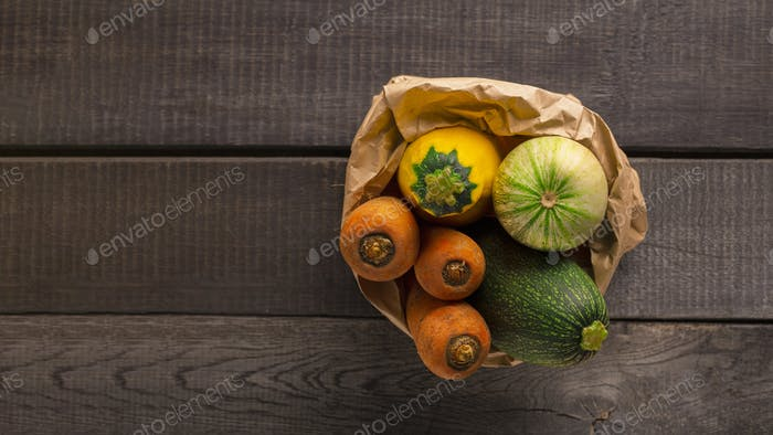 Organic vegetables in paper package on wooden background