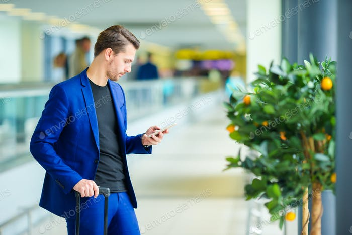 Young man in airport with baggage waiting boarding