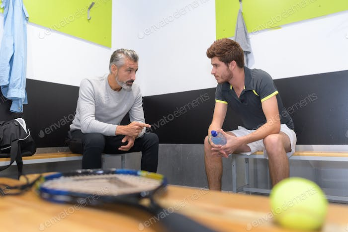 tennis coach talking to player in changing room