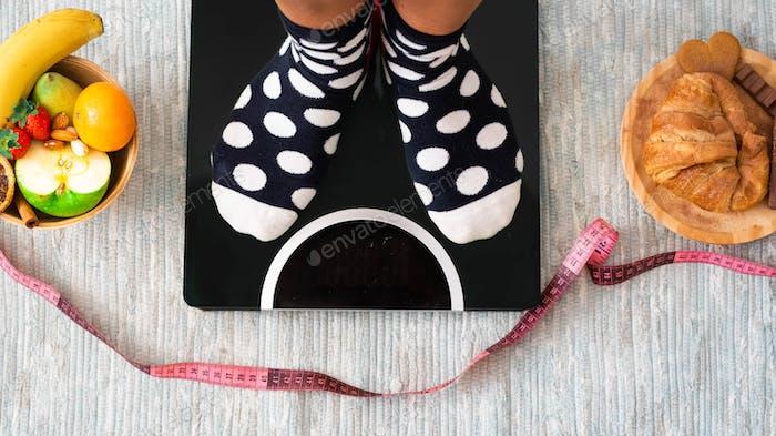 Nahaufnahme von Füßen auf einer Waage, die sucht, wie hoch ist ihr Gewicht und ob sie Gewicht verloren hat